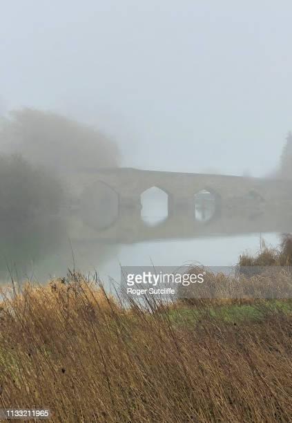 ancient stone bridge in mist - theems stockfoto's en -beelden