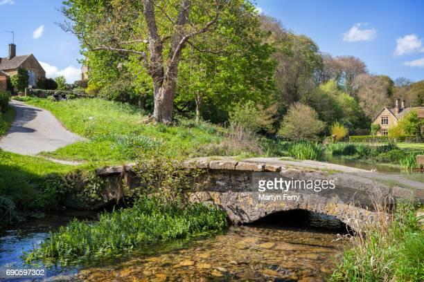 ancient stone footbridge in upper slaughter, the cotswolds, gloucestershire, uk - steen bouwmateriaal stockfoto's en -beelden