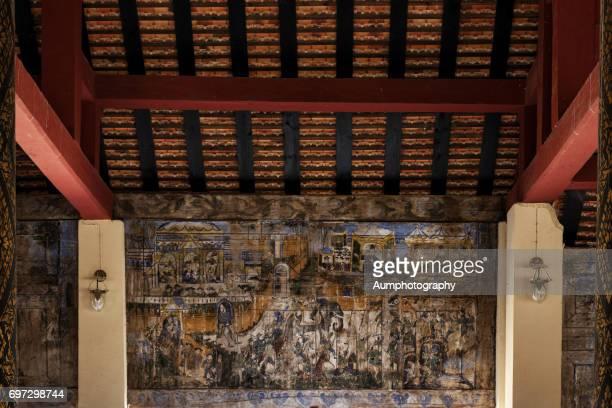 Ancient Thai mural painting on wooden temple wall at Wat Phra That Lampang Luang in Lampang, Thailand.