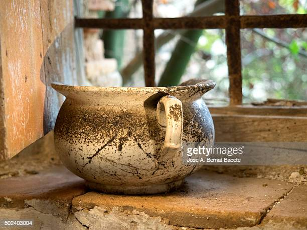 Ancient urinal of ceramics close to a window of a left house