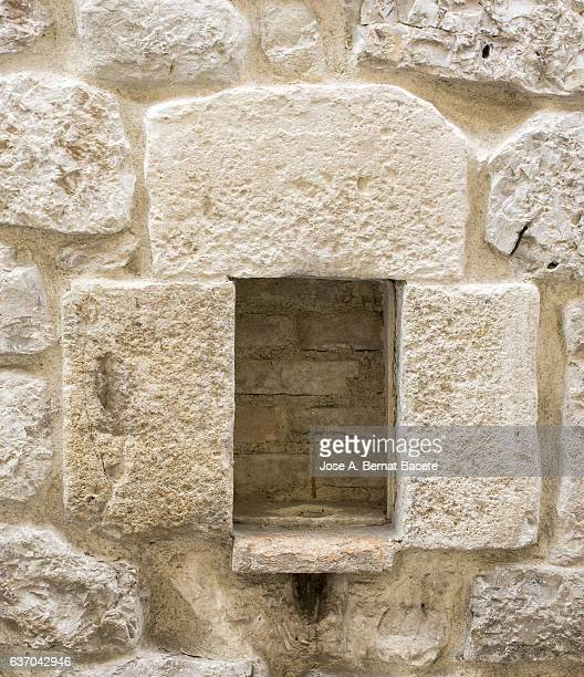 Ancient wall with a window of wood with adornments of stone of medieval origin