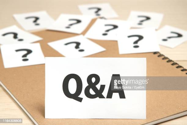 q and a text and question marks on table - domanda e risposta foto e immagini stock