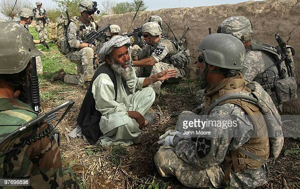 And Afghan Army soldiers question a farmer after a firefight with Taliban insurgents on March 14, 2010 at Howz-e-Madad in Kandahar province,...