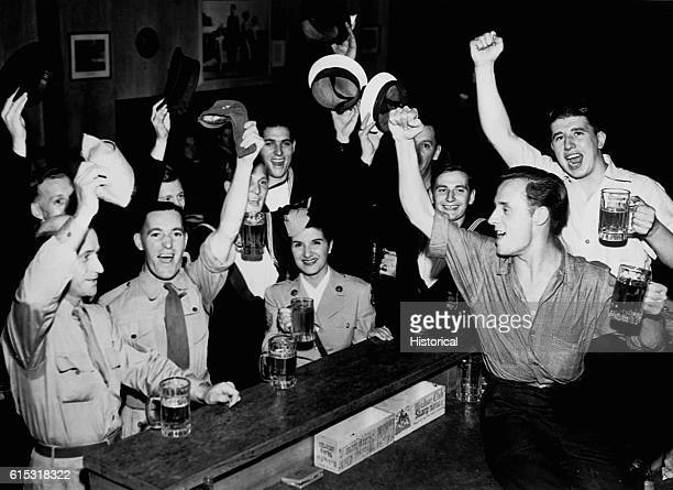 US and British servicemen gather at a club to celebrate Japan's unconditional surrender