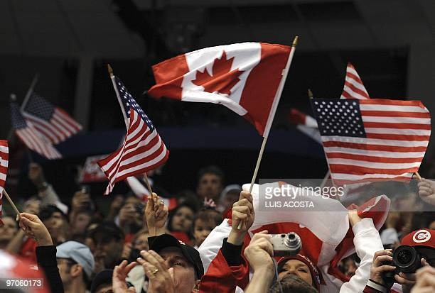 USA and Canadian fans wave their national flags during the Women's Gold Medal Hockey game between USA and Canada at the Canada Hockey Place during...