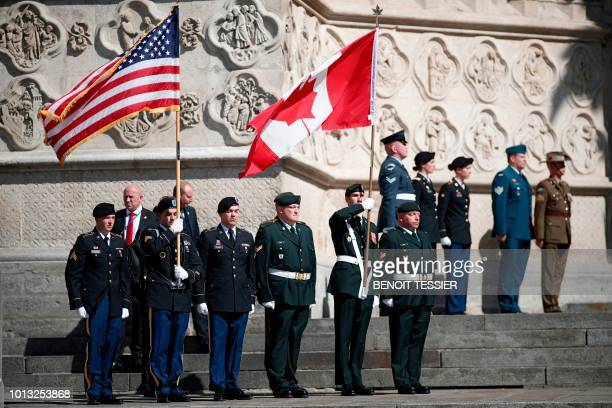 US and Canadian flag bearers stand at attention outside the cathedral after a religious ceremony to mark the 100th anniversary of the World War I...