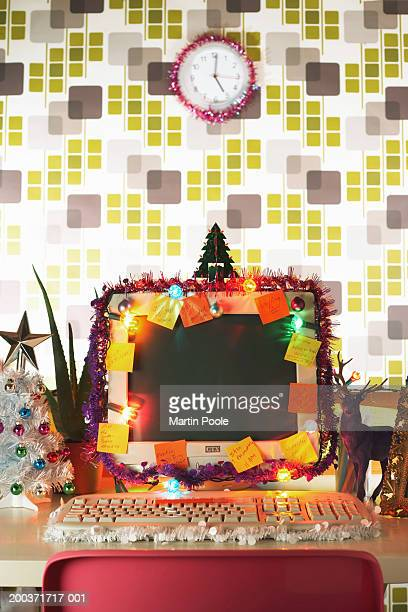 PC and clock surrounded by Christmas decorations