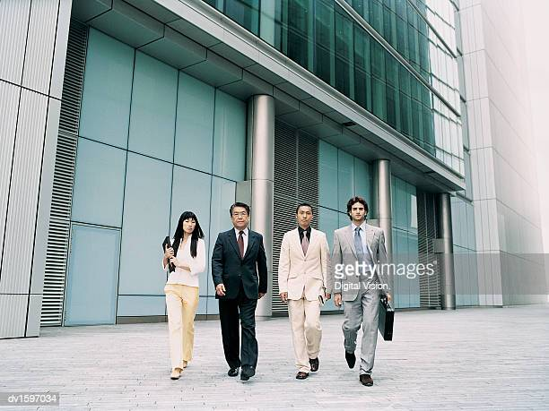 CEO and Colleagues Walking Outdoors in a Line