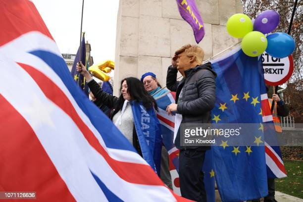 UKIP and EDL supporters one wearing a Donald Trump mask stand amongst anti Brexit supporters outside the Houses of Parliament Westminster on December...