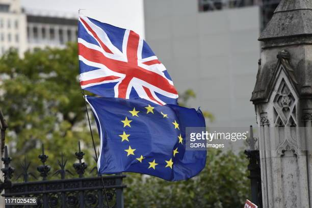 UK and EU flags hang outside Parliament while UK MPs get back to work