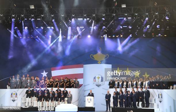 US and European team players stand during the playing of national anthems at the opening ceremony of the 42nd Ryder Cup at Le Golf National Course at...