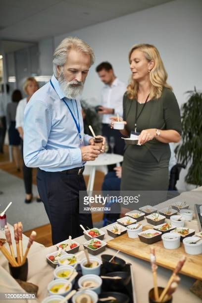 ceo and female executive selecting small dishes at buffet - launch event stock pictures, royalty-free photos & images