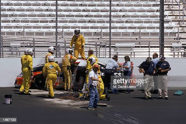 T and firefighters attend to Adam Petty and his car after Petty spunout and crashed into a concrete barrier during practice for the Busch 200 part of...