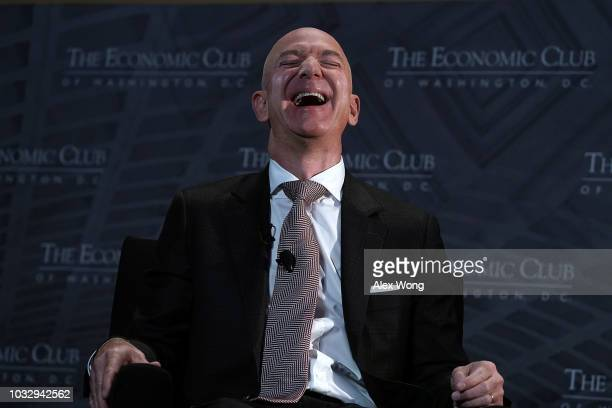 CEO and founder of Amazon Jeff Bezos laughts as he participates in a discussion during a Milestone Celebration dinner September 13 2018 in Washington...