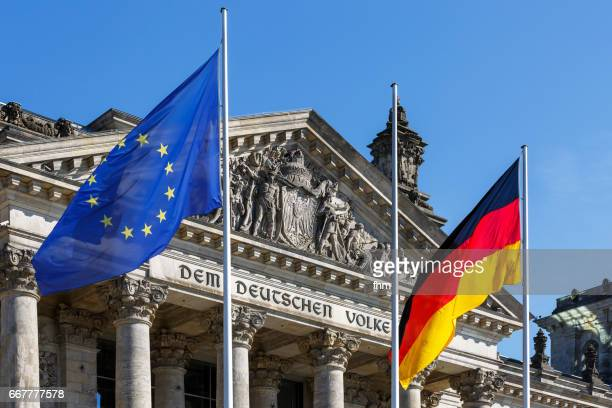 EU- and german flag with the famous inscription on the architrave on the west portal of the Reichstag building in Berlin: 'Dem Deutschen Volke'