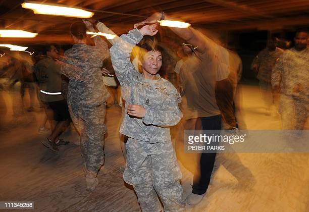 US and ISAF personnel dance the salsa in the evening at southern Kandahar airfield on March 30 2011 Around 140000 foreign troops are deployed in...