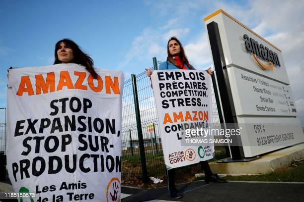 and Les Amis de la Terre activists block an Amazon centre in BretignysurOrge on November 28 to protest against the company's labour policies and...