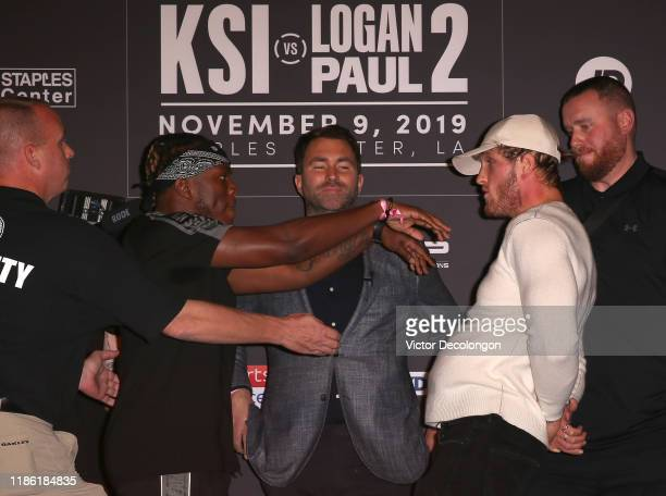 and Logan Paul face off onstage while promoter Eddie Hearn looks on during the KSI VS Logan Paul 2 Final Press Conference at TAO Hollywood on...
