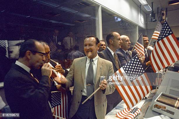 NASA and Manned Spacecraft Center officials join the flight controllers in celebrating the conclusion of the Apollo 11 mission From left foreground...