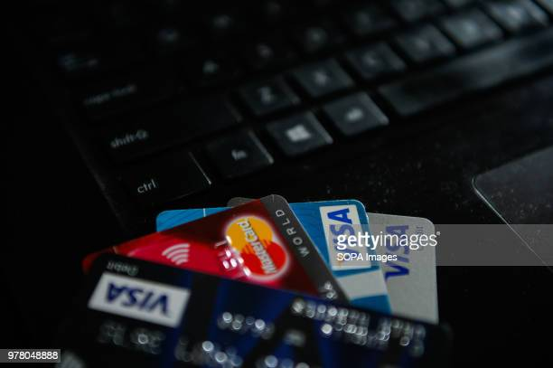 VISA and Mastercards cards are seen on the top of a laptop keyboards