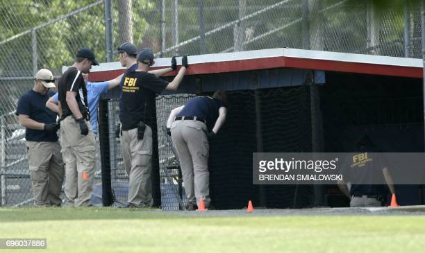 FBI and other law enforcement officials inspect the crime scene after a shooting during a practice of the Republican congressional baseball game at...