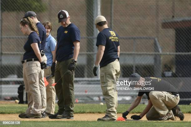 FBI and other law enforcement officials inspect the crime scene after a shooting during a practice for the Republican congressional baseball game at...
