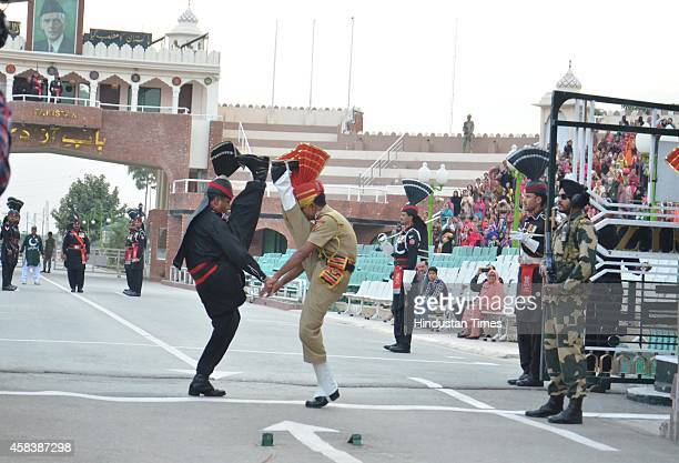 BSF and Pakistan border guards perform high kicks during a flag lowering ceremony at Attari Border on November 4 2014 in Amritsar India At least 60...