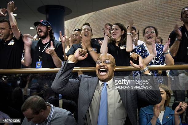 And project staff react with others as telemetry is received from the New Horizons probe at the Johns Hopkins University Applied Physics Laboratory...