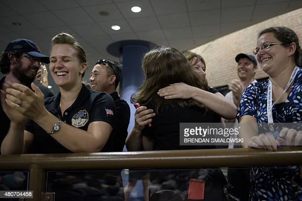 NASA and project staff react with others while telemetry is received from the New Horizons probe at the Johns Hopkins University Applied Physics...