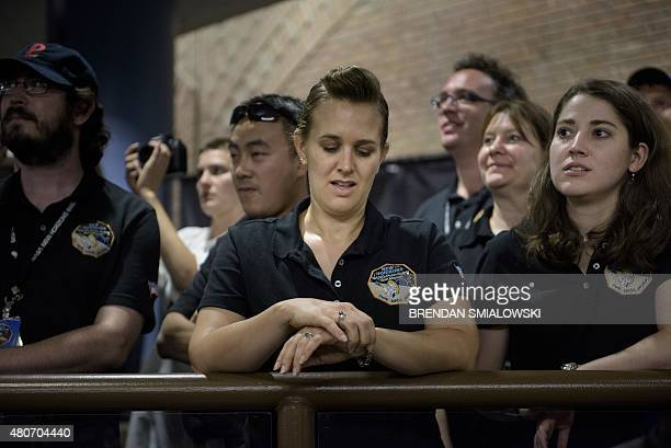 NASA and project staff wait for telemetry to be received from the New Horizons probe at the Johns Hopkins University Applied Physics Laboratory July...
