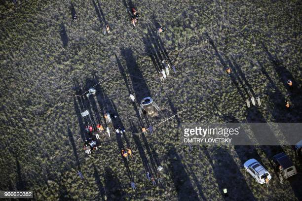 NASA and Russian Emergency teams gather at the Russian Soyuz MS07 space capsule after its landing about 150 km southeast of the Kazakh town of...