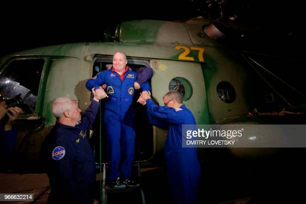 NASA and Russian Emergency teams help US astronaut Scott Tingle past an helicopter after its landing onboard the Russian Soyuz MS07 space...