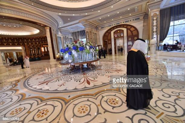 US and Saudi officials walk in the hallway of the Ritz Carlton hotel in the capital Riyadh on May 21 during a visit of the US president / AFP PHOTO /...