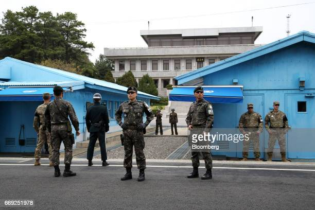 US and South Korean soldiers foreground and North Korean soldiers background stand guard next to the meeting rooms that straddle the border between...