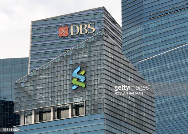 and Standard Chartered bank logo are seen on the building at Marina Bay financial district in Singapore on July 21 2016 Singapore revealed on July 21...