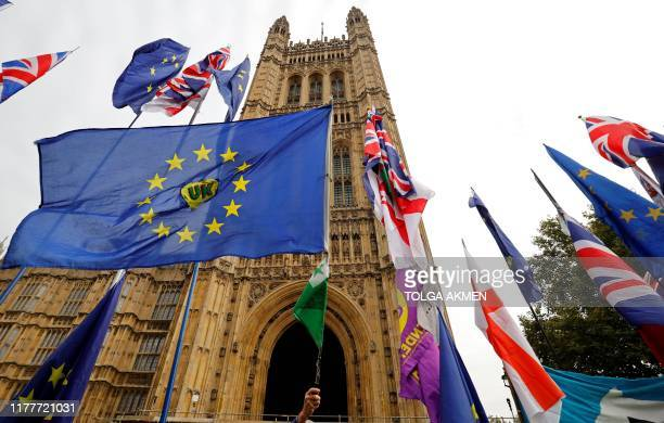 EU and Union flags belonging to Brexit activists fly outside the Houses of Parliament in London on October 23 2019 British Prime Minister Boris...