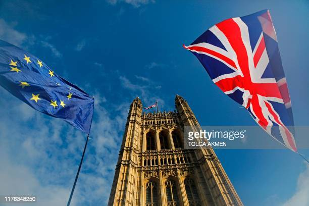 TOPSHOT EU and Union flags flutter in the breeze in front of the Victoria Tower part of the Palace of Westminster in central London on October 17...