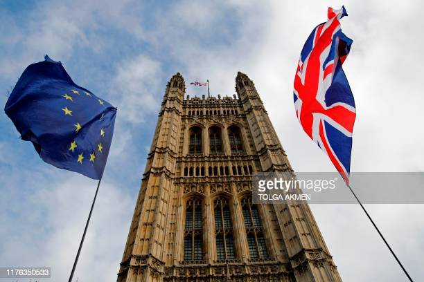 EU and Union flags flutter in the breeze in front of the Victoria Tower part of the Palace of Westminster in central London on October 17 2019...