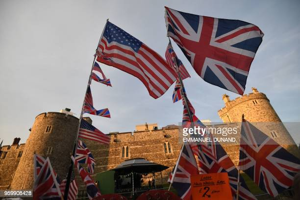 US and Union flags wave in the evening sunlight beside Windsor Castle in Windsor on May 18 the eve of Britain's Prince Harry's royal wedding to US...