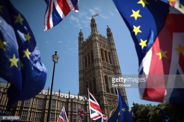 EU and Union Jack flags are waved as antiBrexit demonstrators gather outside the Houses of Parliament on June 11 2018 in London England The EU...