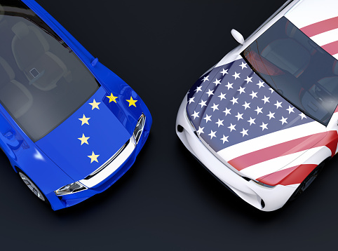 EU and US flags on two automobiles hood. black background 997294706