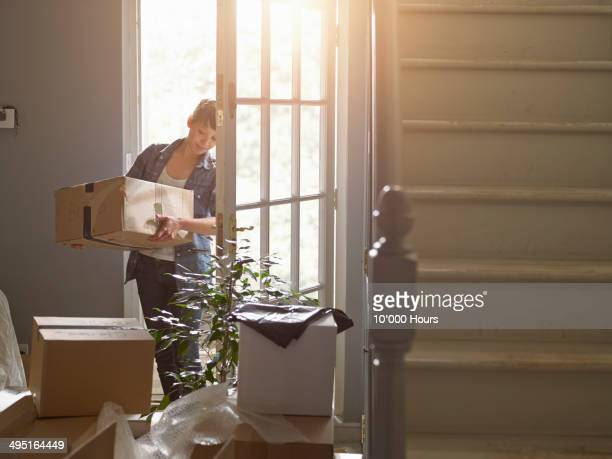 and woman carrying a packing box into her new home - new home stock pictures, royalty-free photos & images