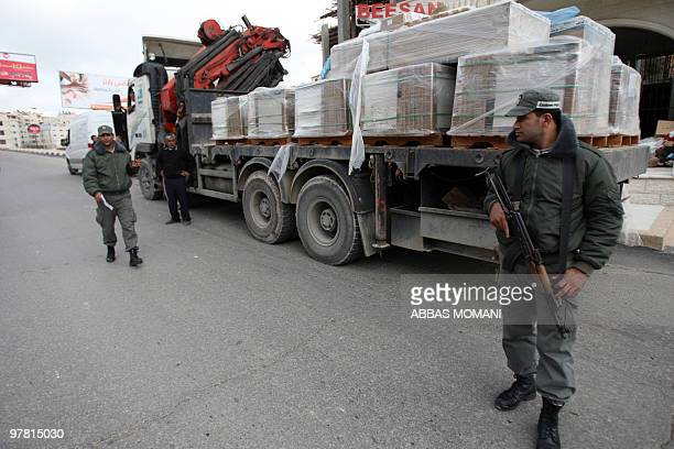 EZZEDINE and YOAV LEMMER Palestinian customs policemen stop a loaded truck to search if it's carrying products from Jewish settlements in West Bank...