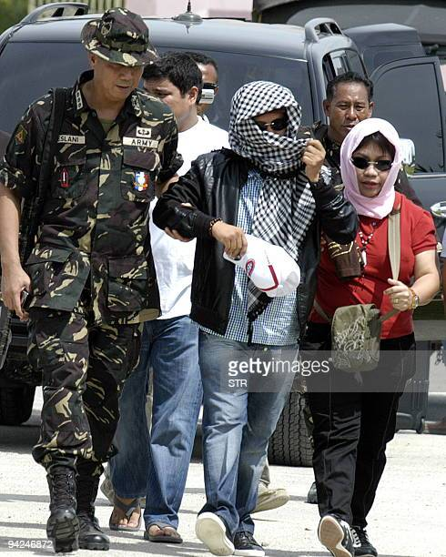 Andal Ampatuan accompanied by his wife is escorted by military personnel to a helicopter after his surrendering to authorities in Shariff Aguak...