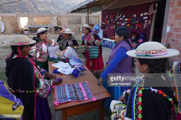 Andean women prepare to sell protective masks with traditional themes on June 12 2020 in Ayata Bolivia Andean women sew and embroider face masks with...