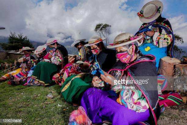 Andean women wearing protective masks sew and embroider on June 12 2020 in Ayata Bolivia Andean women sew and embroider face masks with traditional...