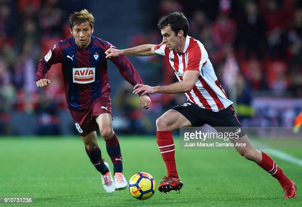 Ander Iturraspe of Athletic Club being followed by Takashi Inui of SD Eibar during the La Liga match between Athletic Club and Eibar at Estadio San...