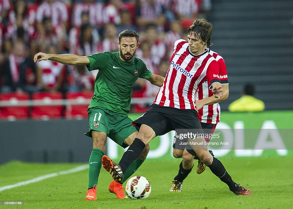 Ander Iturraspe of Athletic Club Bilbao duels for the ball with Jose Luis Morales of Levante UD the La Liga match between Athletic Club and Levante UD at San Mames Stadium on August 30, 2014 in Bilbao, Spain.