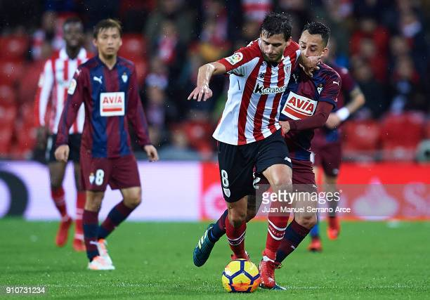 Ander Iturraspe of Athletic Club competes for the ball with Fabian Orellana of SD Eibar during the La Liga match between Athletic Club and Eibar at...