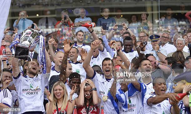 Anderlecht's Belgian defender Guillaume Gillet lifts the Championship cup during his team's celebrations as RSC Anderlecht won the Belgian...